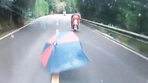 开车注意摩托车带伞的