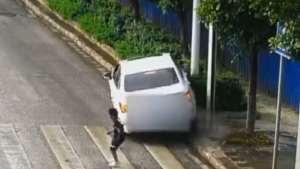男孩奔跑过马路差点撞上路过车辆,车辆撞向路边花坛
